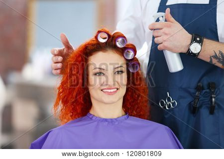 Beautiful girl making curlers in hairdressing salon
