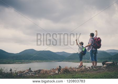 Father And Son Standing Near The Lake.