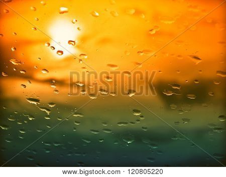 Water drops on a window glass after the rain. The sky with clouds and sun on background
