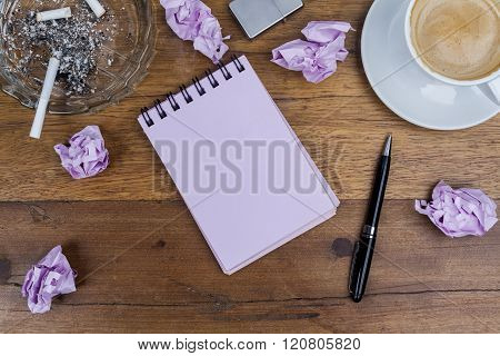 Notebook pen coffee ashtray cigarette crumpled paper on wooden table
