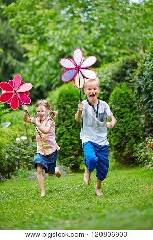 Two happy children running with windmills in garden in summer