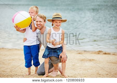 Happy father playing with two siblings on beach of a lake in summer