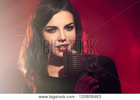 Attractive female singer on red background, close up