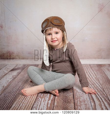 cute little girl-pilot sitting on the floor in pilot hat