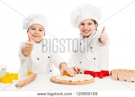 two little smiling chefs cutting dough with forms with thumbs up