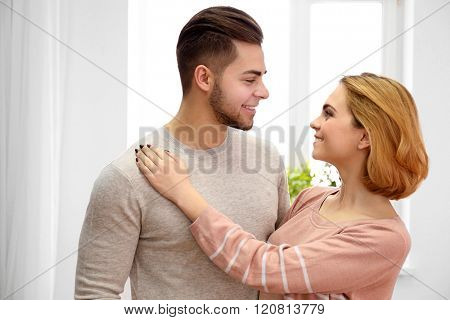 Young couple in love looking at each other beside the window