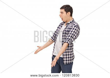Studio shot of an angry young man arguing with someone isolated on white background