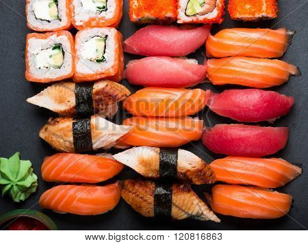 Various kinds of sushi served on black stone. Sushi Set sashimi and sushi rolls, top view