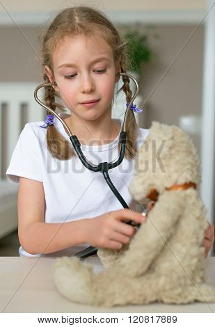 Cute little girl playing in doctor with her toy.** Note: Visible grain at 100%, best at smaller sizes