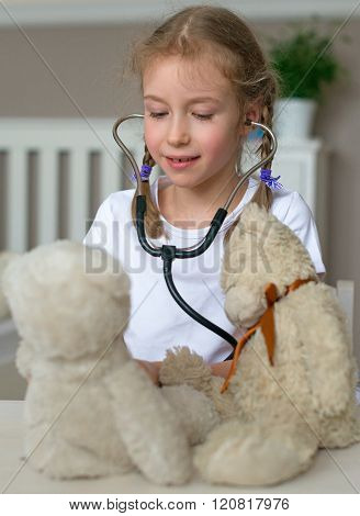 Cute little girl playing in doctor with her toys.