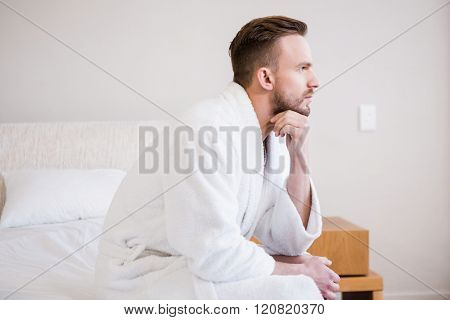 Serious man in bathrobe looking away in bedroom
