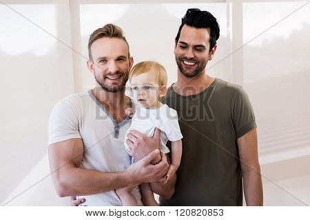 Smiling gay couple with child at home