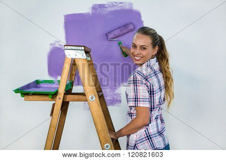 Smiling woman painting a wall in new house