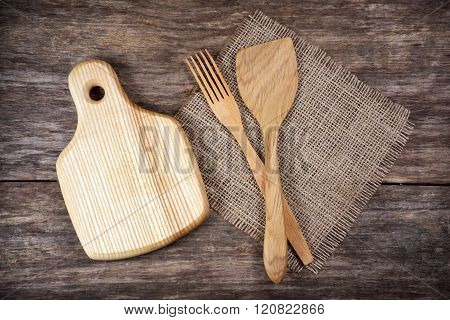 Empty chopping board and kitchen utensils on wooden table background