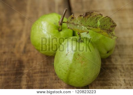 Closeup Three Ripe Green Guavas On Brown Table