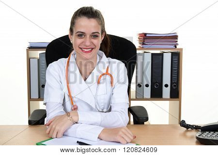 Young Smiling Doctor Sitting At The Desk  With Arms Crossed