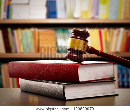 Judge gavel and books on table on book shelves background