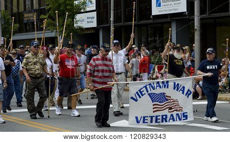 Bangor, Maine/USA-July 4: Vietnam Veterans raise their walking canes in salute to officials as they march in the 4th of July Parade in 2015 in Bangor, Maine.
