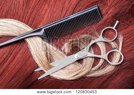 Hairdresser's scissors with comb and varicolored strands of hair, close up