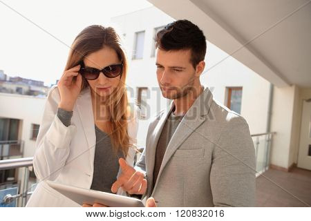 Young couple using tablet computer in corridor of apartment house.