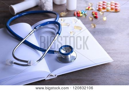 Stethoscope with open book and pills on wooden background. Medical literature concept
