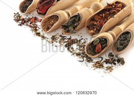 Variety of dry tea in wooden scoops isolated on white, copy space