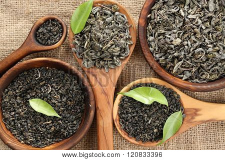 Dry tea with green leaves in wooden spoons on burlap background