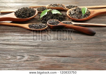 Dry tea with green leaves in wooden spoons on table background, copy space