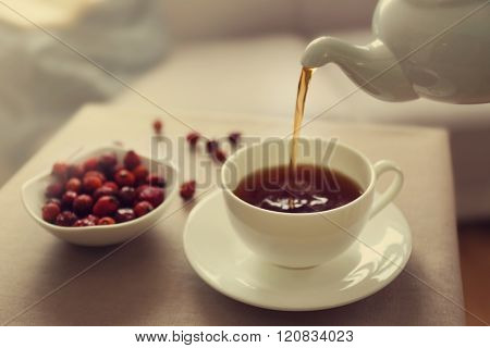 Pouring rose hip tea into cup, home atmosphere