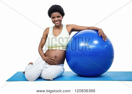 Pregnant woman with exercise ball on white background