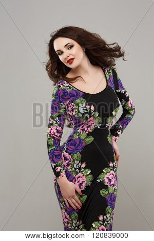 pretty young girl wearing a flower printed dress. fashion studio photo of beautiful girl with long hair in elegant dress with print of flower's headband. beautiful girl in fashionable dress.