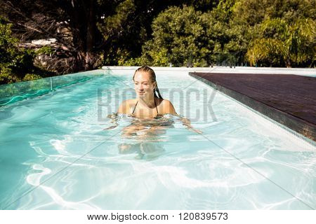 Smiling blonde in the pool in a sunny day