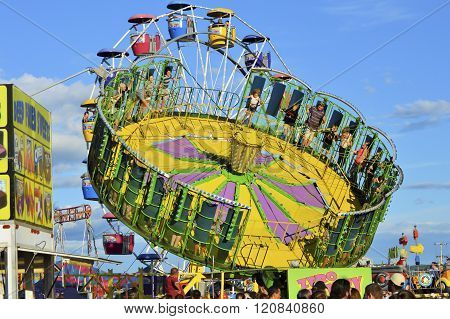 Bangor, Maine/USA-August 6: Two colorful fair rides seem to intersect against a blue sky at the Bangor State Fair on August 6, 2015 in Bangor, Maine.