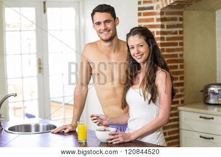 Portrait of young couple standing near kitchen worktop and having breakfast together