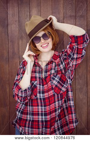 smiling woman wearing a trilby and sunglasses against a wooden background