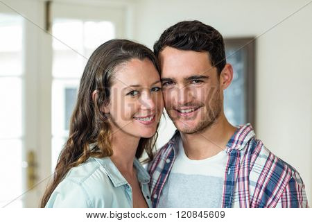 Portrait of couple standing cheek to cheek and smiling in living room