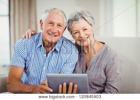 Portrait of senior couple holding digital tablet and smiling while sitting on sofa in living room