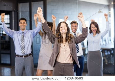 Confident businessman standing in front while his colleagues standing behind him in office