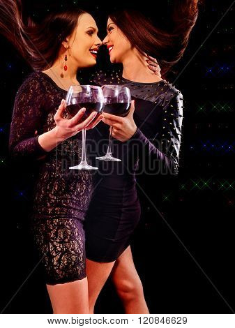 Lesbian women drinking red wine and dancing on nightclub on black background.