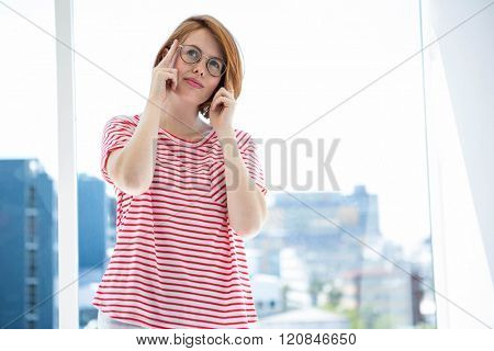 Cute red haired hipster with glasses in front of a window