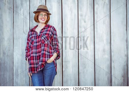smiling hipster woman with her hand in her pocket, against a wooden background