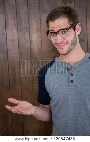 Handsome hipster wearing nerd glasses on wooden background