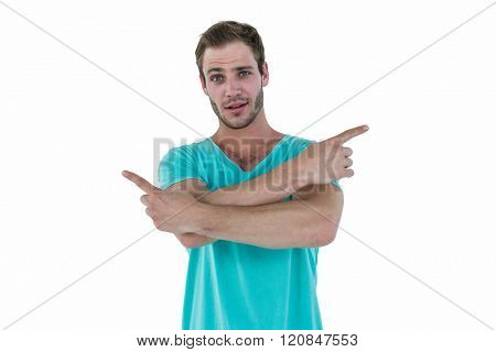 Hipster pointing sideways with arms crossed on white background