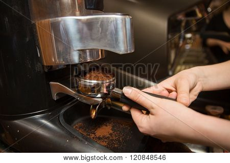equipment, coffee shop, people and technology concept - close up of woman making coffee by machine at cafe bar or restaurant kitchen