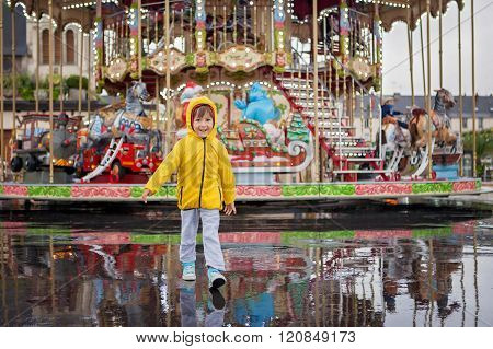 Sweet Child, Boy Watching Carousel In The Rain, Wearing Yellow Raincoat