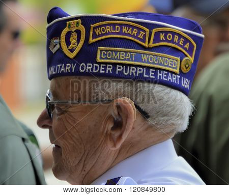 Bangor, Maine/USA-May 25: A WWII-Korean War Veteran stands proudly at a Memorial Day Parade on May 25, 2015 wearing a decorated hat showing his military journey.