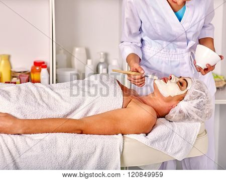 Lying woman wearing medical hat middle-aged take facial and neck clay mask in spa salon.