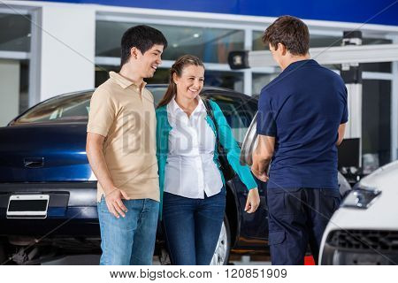 Couple Discussing Over Alloy With Mechanic
