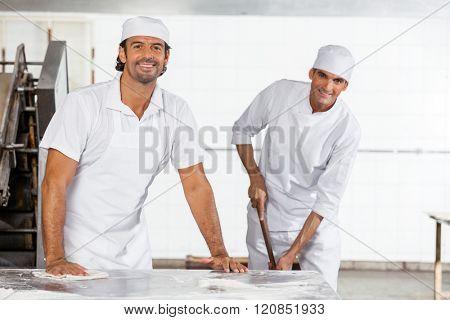 Happy Male Baker's In Uniform Cleaning Bakery
