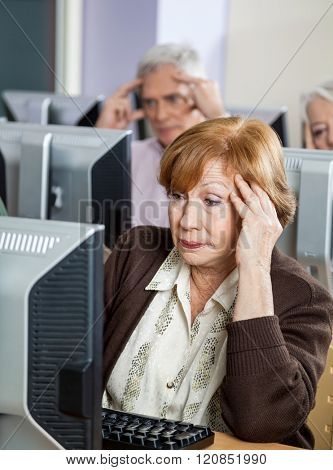 Tensed Senior Woman Looking At Computer In Classroom